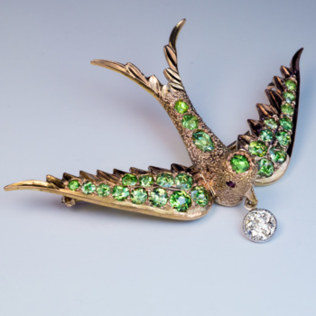 antique bird shaped brooch pin set with demantoid garnets and an old cut diamond