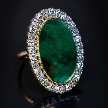 antique ring set with cabochon cut emerald surrounded by diamonds