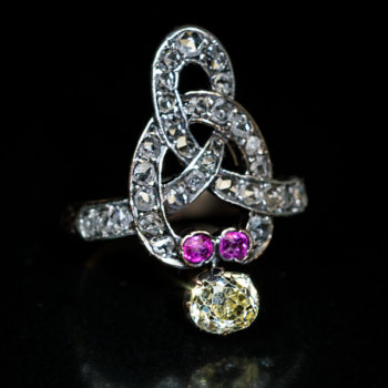 Victorian antique knot ring set with a fancy color old mine cut diamond, rose cut diamonds and rubies